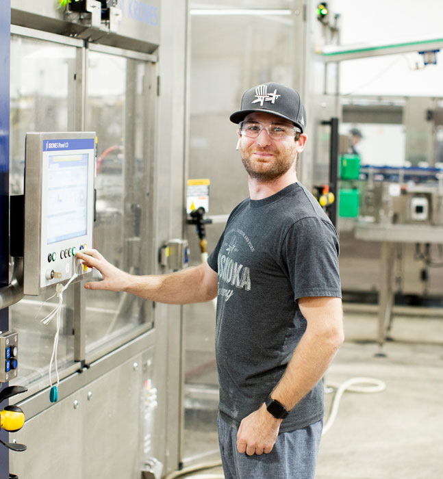Person operating computer on canning line.