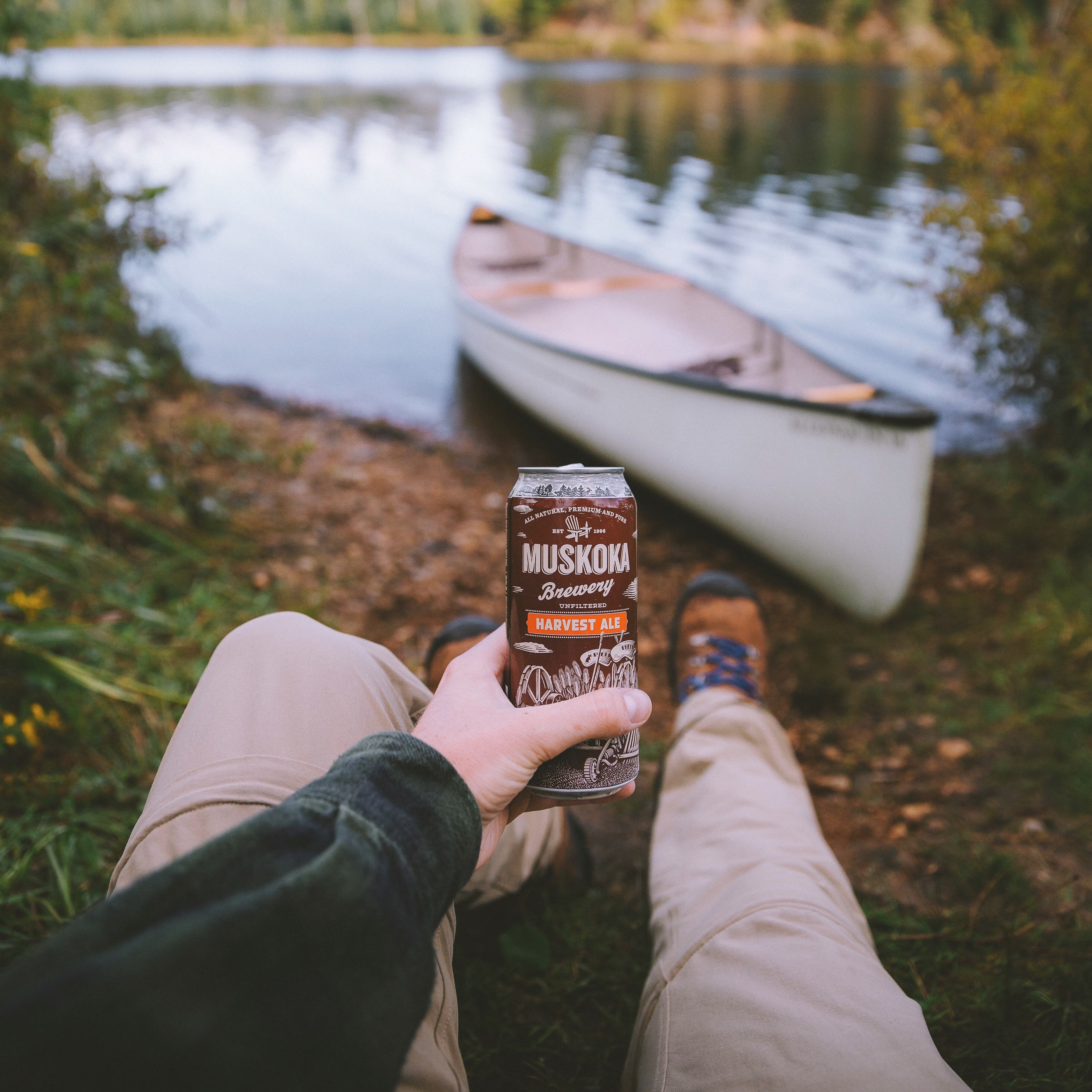 Harvest Ale in front of a canoe and lakeview.