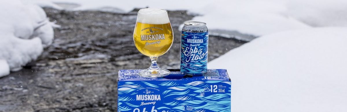 Ebb and Flow in a breughel and short can sitting on top of the 12-pack by an icy river flow.