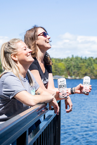 Girls laughing on a dock with DOcker Gin & Sodas in hand.