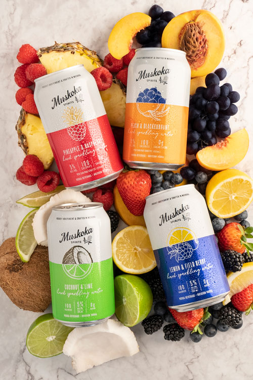 Cans of hard sparkling water on a bed of fruit.