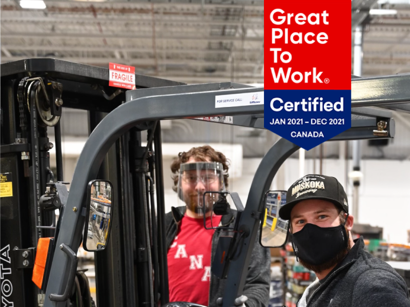 Two people around a fork lift with Great Place to Work Certification Badge in top right corner.
